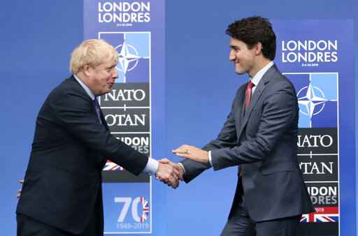 FILE - In this Wednesday, Dec. 4, 2019 file photo, British Prime Minister Boris Johnson, left, welcomes Canadian Prime Minister Justin Trudeau during official arrivals for a NATO leaders meeting at The Grove hotel and resort in Watford, Hertfordshire, England. The U.K. has signed an interim trade deal with Canada _ a rollover measure meant to cement the trading relationship as the government prepares of life outside the European Union. While Britain formally withdrew from the EU in January, it continues to trade with other countries under the bloc's umbrella during a transition period that is scheduled to end Dec. 31. (AP Photo/Francisco Seco, File)