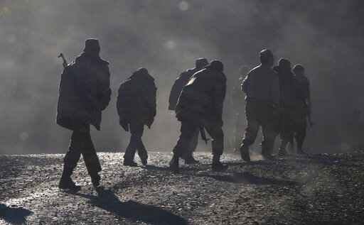 FILE - In this Sunday, Nov. 8, 2020 file photo, ethnic Armenian soldiers walk along the road near the border between Nagorno-Karabakh and Armenia. Azerbaijan on Thursday Sept. 23, 2021, filed a case at the United Nations' top court accusing neighboring Armenia of a