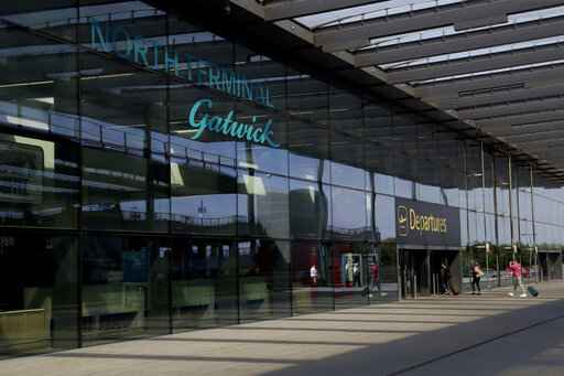 FILE  - In this Wednesday, July 22, 2020 file photo, passengers walk into the Departures entrance at the North Terminal of Gatwick Airport near Crawley, just south of London. With all British schools now closed for the summer, airports and airlines are looking a tad more normal this Saturday, July 24, 2021 though the number of families heading off for warmer climes remains way down on the levels seen before the coronavirus pandemic struck. (AP Photo/Matt Dunham, File)