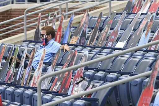 A fan sits among cardboard cutouts of other fans before the first half of an NCAA college football game between Mississippi and Florida in Oxford, Miss., Saturday, Sept. 26, 2020. (AP Photo/Thomas Graning)