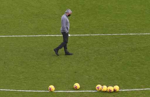 Tottenham Hotspur manager Jose Mourinho wearing a protective face mask during the warm up before the English Premier League soccer match between Sheffield United and Tottenham Hotspur at the Bramall Lane stadium in Sheffield, England, Sunday, Jan.17, 2021. (Stu Forster/Pool via AP)