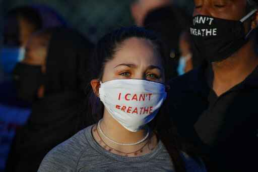 Madeline Curry attends a protest with her father outside the Minneapolis 5th Police Precinct while wearing a protective mask that reads
