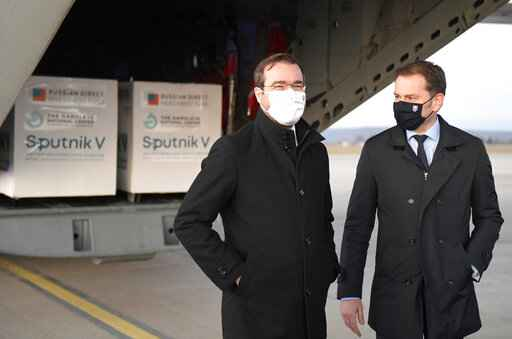 FILE - In this Monday March 1, 2021 file photo, Slovak Prime Minister Igor Matovic, right, and Health Minister Marek Krajci at Kosice Airport, Slovakia, as Russia's Sputnik V coronavirus vaccine arrives. Two parties in Slovakia'€™s ruling coalition called on the conservative prime minister to resign to open the way for a reconstruction of the government amid a political crisis triggered by a secret deal to buy Russia's coronavirus vaccine. (Frantisek Ivan/TASR via AP, File)