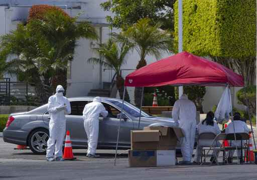 Unidentified Los Angeles residents are admistered with a test for COVID-19 while in their vehicles inside the Crenshaw Christian Center in South Los Angeles Wednesday, March 25, 2020. With California virus cases surging, Gov. Gavin Newsom said his stay-at-home order for 40 million Californians may stay in place into May.  (AP Photo/Damian Dovarganes)