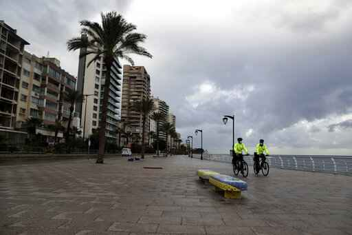 Police bike officers patrol on the empty waterfront promenade as the country starts a new lockdown, in Beirut, Lebanon, Thursday, Jan. 14, 2021. Lebanese authorities began enforcing an 11-day nationwide shutdown and round the clock curfew Thursday, hoping to limit the spread of coronavirus infections spinning out of control after the holiday period. (AP Photo/Bilal Hussein)