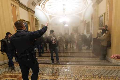 FILE - In this Jan. 6, 2021, file photo, smoke fills the walkway outside the Senate Chamber as supporters of President Donald Trump are confronted by U.S. Capitol Police officers inside the Capitol in Washington. With riot cases flooding into Washington's federal court, the Justice Department is under pressure to quickly resolve the least serious cases. (AP Photo/Manuel Balce Ceneta, File)