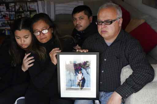 Cassandra Quinto-Collins, second from left, holds a photo of her son, Angelo Quinto, while sitting with daughter Bella Collins, left, son Andrei Quinto, center, and husband Robert Collins during an interview in Antioch, Calif., Tuesday, March 16, 2021. Angelo Quinto died three days after being restrained on Dec. 23, 2020, in police custody while having a mental health crisis. Lawmakers in several states are proposing legislation that would require more training for police in how to interact with someone in a mental crisis following some high-profile deaths. (AP Photo/Jeff Chiu)