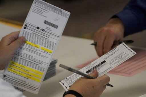 FILE - In this Nov. 3, 2020 file photo, workers count Milwaukee County ballots on Election Day at Central Count in Milwaukee. President Donald Trump's campaign has paid $3 million for a recount of two heavily Democratic Wisconsin counties, saying Wednesday, Nov. 18, 2020, that they were the site of the