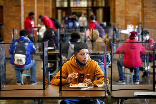 FILE - In this March 31, 2021, file photo, freshman Hugo Bautista eats lunch separated from classmates by plastic dividers at Wyandotte County High School in Kansas City, Kan., on the first day of in-person learning. With a massive infusion of federal aid coming their way, schools across the U.S. are weighing how to use the windfall to ease the harm of the pandemic - and to tackle problems that existed long before the coronavirus. (AP Photo/Charlie Riedel, File)