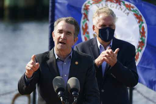 Virginia Gov. Ralph Northam, left, gestures as he speaks during a news conference along with former Gov. and Democratic gubernatorial candidate, Terry McAuliffe, right, at Waterside in Norfolk, Va., Thursday, April 8, 2021. Northam endorsed McAuliffe for governor. (AP Photo/Steve Helber)
