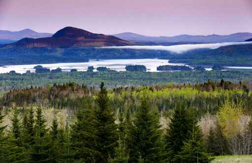 FILE - In this Tuesday, May 28, 2019, file photo is a view of Attean Pond near Jackman, Maine. Central Maine Power's controversial hydropower transmission corridor would be in the vicinity of this view from a scenic pullover. A 150-foot-wide swath of land would extend 53 miles from the Canadian border into Maine's north woods. (AP Photo/Robert F. Bukaty, File)