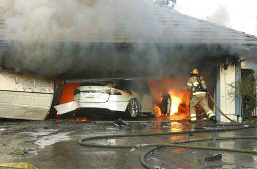 This undated photo provided by National Transportation Safety Board, The Orange County Fire Authority battles a fire on a burning vehicle inside a garage in Orange County, Calif.  When firefighters removed the SUV from the garage to assess the fire , they identified the fuel source as the SUV's high-voltage battery pack.  U.S. safety investigators say electric vehicle fires pose risks to first responders, and manufacturers have inadequate guidelines to keep them safe. (Orange County Sheriff's Department/National Transportation Safety Board via AP)