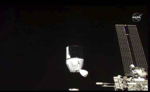 This photo provided by NASA shows SpaceX's Dragon undocking from International Space Station on Tuesday, Jan. 12, 2021.  SpaceX's Dragon cargo capsule undocked with 12 bottles of Bordeaux wine and hundreds of snippets of Merlot and Cabernet Sauvignon vines. The capsule is aiming for a splashdown in the Gulf of Mexico off the Florida coast Wednesday night. (NASA via AP)