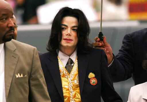 FILE - In this May 25, 2005, file photo, Michael Jackson arrives at the Santa Barbara County Courthouse for his trial in Santa Maria, Calif. On Monday, May 3, 2021, a U.S. tax court handed a major victory to Jackson's estate in a years-long battle, finding that the IRS inflated the value of Jackson's assets and image at the time of his 2009 death. (Aaron Lambert/Santa Maria Times via AP, Pool, File)