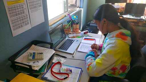 This photo provided by Charles Timtim shows his daughter, name withheld by parents, doing schoolwork from home in Waipahu, Hawaii, Tuesday, Sept. 22, 2020. Timtim's mother doesn't think it's safe for her daughter to be back at school but she also doesn't want her exposed to an online learning program called Acellus that misspelled and mispronounced the last queen to rule the Hawaiian kingdom. Parents spotting questionable content on Acellus is forcing some school districts across the country to reconsider the program or stop using it. (Charles Timtim via AP)