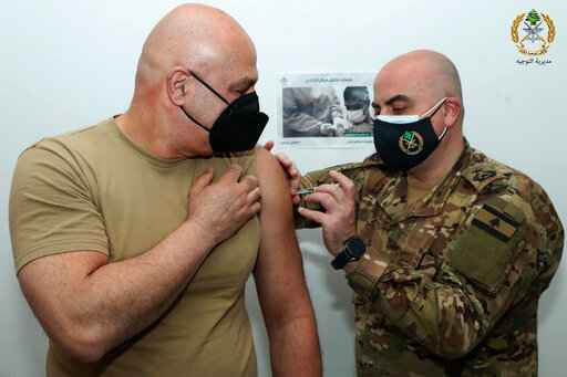 In this photo released by the Lebanese Army official website, Lebanese Army Commander Gen. Joseph Aoun, receives a Sinopharm COVID-19 vaccine, at one of the military vaccination centers, in Beirut, Lebanon, Thursday, April 8, 2021. The Lebanese army said Aoun was the first to get the vaccine and that thousands of soldiers will be vaccinated in the coming weeks. Lebanon received a gift of 90,000 Sinopharm shots from China last week. (Lebanese Army Website via AP)