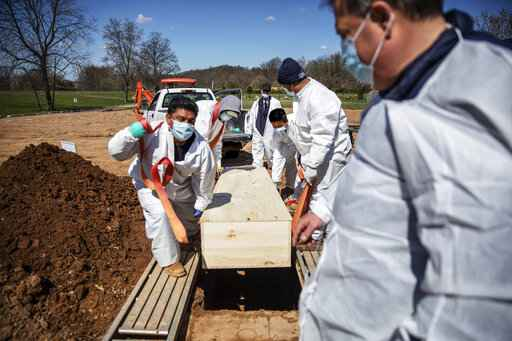 FILE - In this April 6, 2020, file photo, gravediggers lower the casket of someone who died of coronavirus at the Hebrew Free Burial Association's cemetery in the Staten Island borough of New York. The U.S. death toll from COVID-19 has topped 500,000 - a number so staggering that a top health researchers says it is hard to imagine an American who hasn't lost a relative or doesn't know someone who died. (AP Photo/David Goldman, File)