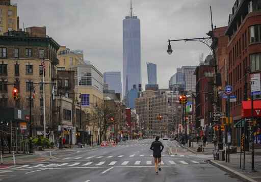A lone jogger run on a partially empty 7th Avenue, resulting from citywide restrictions calling for people to stay indoors and maintain social distancing in an effort to curb the spread of COVID-19, Saturday March 28, 2020, in New York. President Donald Trump says he's considering a quarantine affecting residents of the state and neighboring New Jersey and Connecticut amid the coronavirus outbreak, but�New York Gov. Andrew Cuomo said that roping off states would amount to