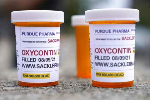 FILE - In this Aug. 9, 2021, file photo, fake pill bottles with messages about OxyContin maker Purdue Pharma are displayed during a protest outside the courthouse where the bankruptcy of the company is taking place in White Plains, N.Y. A federal judge on Wednesday, Oct. 13 allowed Purdue Pharma to resume its work carrying out the recent $10 billion settlement plan that allowed the Oxycontin maker to emerge from bankruptcy. (AP Photo/Seth Wenig, File)