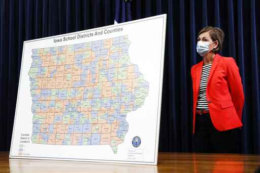 FILE - In this  July 30, 2020, file photo, Iowa Gov. Kim Reynolds listens to a question during a news conference on the state's guidance for returning to school in response to the coronavirus outbreak in Des Moines, Iowa. An aggressive push by Reynolds to reopen schools amid a worsening coronavirus outbreak has descended into chaos, with some districts and teachers rebelling and experts questioning the scientific benchmarks being used by the state to make decisions. (AP Photo/Charlie Neibergall, File)