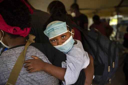 A little girl with teary eyes holds is carried by a woman who was deported from the U.S. border with Mexico at Toussaint Louverture International Airport in Port-au-Prince, Haiti, Monday, Sept. 20, 2021. The U.S. is flying Haitians camped in a Texas border town back to their homeland. (AP Photo/Rodrigo Abd)