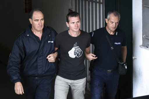 FILE - A Russian man identified as Alexander Vinnik, center, is escorted by police officers from the courthouse at the northern Greek city of Thessaloniki, in this Friday, Sept. 29, 2017, file photo. Vinnick, convicted of laundering $160 million in criminal proceeds through a cryptocurrency exchange, is currently imprisoned in France and might yield additional information about the intersection of organized cybercrime and the Russian state. (AP Photo/Giannis Papanikos, File)