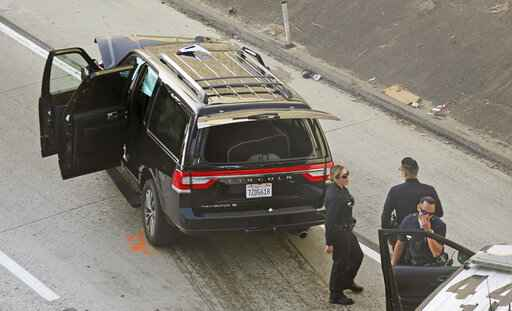 Los Angeles police officers stand after a pursuit of a stolen hearse with with a casket and body inside on Interstate 110 in South Los Angeles Thursday, Feb. 27, 2020.  The hearse was stolen from outside a Greek Orthodox church in East Pasadena on Wednesday night. The Los Angeles County Sheriff's Department says one person is in custody.  (AP Photo/Reed Saxon)