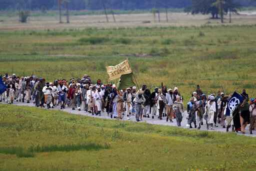 People march through the Bonnet Carre Spillway as they participate in a performance artwork reenacting the largest slave rebellion in U.S. history, in Norco, La., Friday, Nov. 8, 2019. The reenactment was conceived by Dread Scott, an artist who often tackles issues of racial oppression and injustice. (AP Photo/Gerald Herbert)