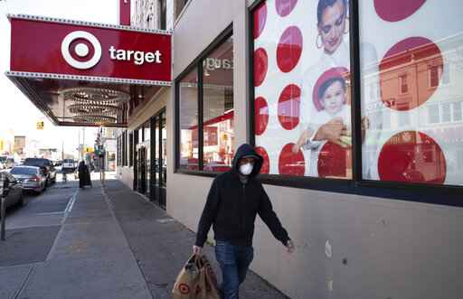 FILE - In this April 6, 2020 file photo, a customer wearing a mask carries his purchases as he leaves a Target store during the coronavirus pandemic, in the Brooklyn borough of New York. Target says it will spend a a total of more than $2 billion at Black-owned businesses by 2025 as part of its effort to advance racial equity. As part of its program, the Minneapolis-based discounter will add products from more than 500 Black-owned businesses across all types of merchandising areas. (AP Photo/Mark Lennihan, File)
