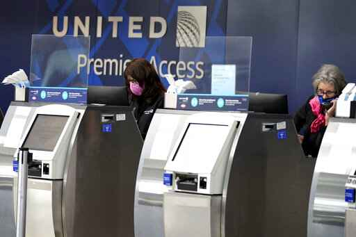 FILE - United Airlines employees work at ticket counters in Terminal 1 at O'Hare International Airport in Chicago, on Oct. 14, 2020. United Airlines said Wednesday, Sept. 8, 2021, that more than half its employees who weren't vaccinated last month have gotten their shots since the company announced that vaccines would be required.  (AP Photo/Nam Y. Huh, File)