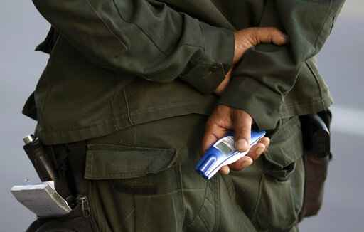 A municipal police officer holds a no-touch forehead thermometer at a checkpoint amid increased restrictions on residents' movements in an effort to curb the spread of the new coronavirus in Niteroi, Brazil, Monday, May 11, 2020. (AP Photo/Silvia Izquierdo)