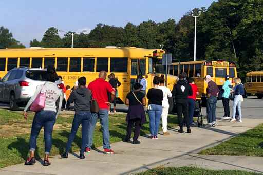 In this Thursday, Oct. 15, 2020, photo voters line up at Mallard Creek High School during the first day of in-person voting ahead of the Nov. 3 elections in Charlotte, N.C. (AP Photo/Laurie Kellman)