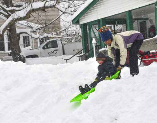 Edisa Weeks gives her 5-year-old nephew, Niko Brown, a push down a hill at the Brattleboro Little League Field, in Brattleboro, Vt., on Monday, Dec. 2, 2019. A final wallop of a seemingly endless winter storm that impacted most of the country over the long holiday weekend is bearing down on the East, dumping heavy snow, shuttering schools and stymieing travel in the region Monday. (Kristopher Radder/The Brattleboro Reformer via AP)