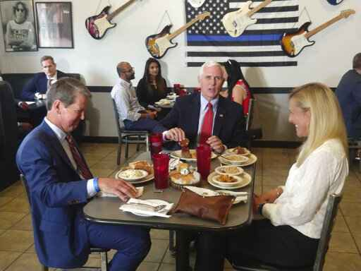 Vice President Mike Pence eats lunch with Georgia Gov. Brian Kemp and his wife Marty Kemp at the Star Cafe, Friday, May 22, 2020, in Atlanta. Pence said Georgia was