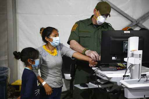 FILE - In this March 30, 2021, file photo, a migrant and her daughter have their biometric data entered at the intake area of the U.S. Department of Homeland Security holding facility, the main detention center for unaccompanied children in the Rio Grande Valley, in Donna, Texas. Migrant families will be held at hotels in the Phoenix area in response to a growing number of people crossing the U.S.-Mexico border, authorities said Friday, April 9, 2021 another step in the Biden administration's rush to set up temporary space for them. (AP Photo/Dario Lopez-Mills, Pool, File)