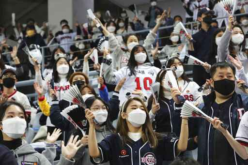 Fans wearing face masks as a precaution against the coronavirus cheer during the Game 4 of the Korean Series, the Korea Baseball Organization's championship round, between Doosan Bears and NC Dinos at Gocheok Sky Dome in Seoul, South Korea, Saturday, Nov. 21, 2020. (AP Photo/Ahn Young-joon)