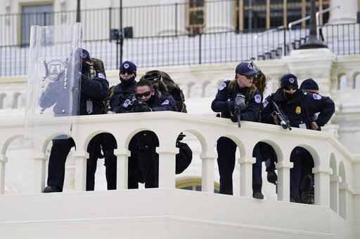 FILE - In this Jan. 6, 2021, file photo, police keep a watch on demonstrators who tried to break through a police barrier at the Capitol in Washington. A blistering internal report by the U.S. Capitol Police describes a multitude of missteps that left the force unprepared for the Jan. 6 insurrection - riot shields that shattered upon impact, expired weapons that couldn't be used, inadequate training and an intelligence division that had few set standards. (AP Photo/Julio Cortez, File)