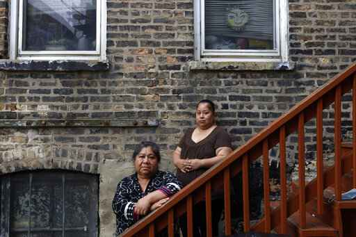 Maria Elena Estamilla, 62, left and her daughter Esmeralda Triquiz pose for a photo June 30, 2021, in Chicago's Pilsen neighborhood. Estamilla's last full medical exam was in 2015 and she sees no options for care as a Mexican immigrant without legal permission to live in the U.S. She's not eligible for Medicare, Medicaid or Affordable Care Act coverage. As a child care worker, she didn't have employer coverage. She can't afford private insurance. (AP Photo/Shafkat Anowar)