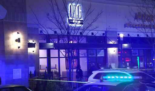 In this image from video provided by WSB-TV, police officers stand outside Old Lady Gang restaurant Friday, Feb. 14, 2020, in East Point, Ga. Three people were shot and wounded at the restaurant just outside Atlanta that's owned by singer and
