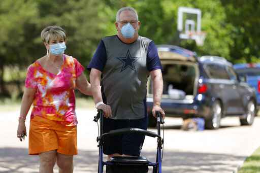 Terri Donelson, left, and her husband, Stephen, walk up their driveway to see friends and family awaiting him at his home in Midlothian, Texas on Friday, June 19, 2020, after his 90-day stay in the Zale Hospital on the UT Southwestern Campus. Donelson's family hadn't left the house in two weeks after COVID-19 started spreading in Texas,�hoping to shield the organ transplant recipient. Yet�one night, his wife found him barely breathing, his skin turning blue,�and called 911. (AP Photo/Tony Gutierrez)