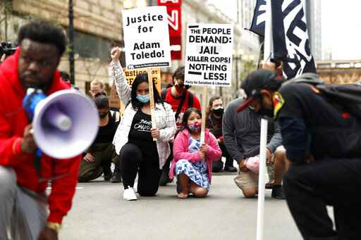 Abigail Garcia, 7, right, takes a knee with her mother Judith Garcia and other protestors during a peaceful protest on Tuesday, April 13, 2021 in downtown Chicago, demanding justice for Daunte Wright and Adam Toledo, who were shot dead by police. (AP Photo/Shafkat Anowar)