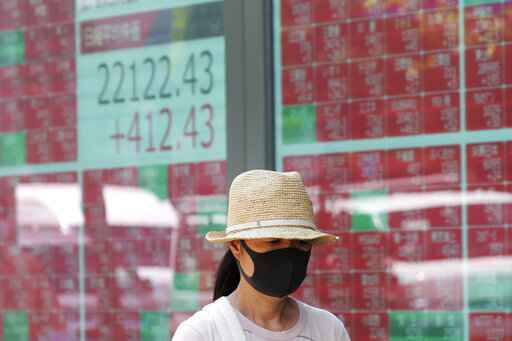 FILE - In this Aug. 3, 2020, file photo, a woman wearing a face mask walks by an electronic stock board of a securities firm in Tokyo.  Shares advanced in Asia on Tuesday, Aug. 11, extending another rally that took the S&P 500 to within striking distance of its all-time high set in February. (AP Photo/Koji Sasahara, File)