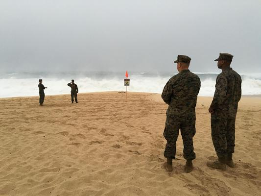 U.S. Marines walk on the beach at Waimea Bay near Haleiwa, Hawaii, where two military helicopters crashed into the ocean about 2 miles offshore, Friday, Jan. 15, 2106.