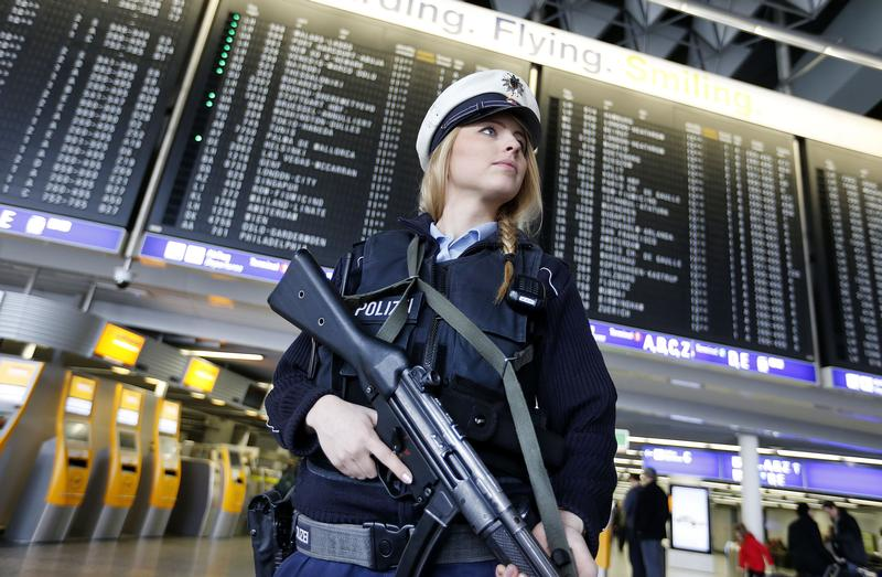 A German police officer guards a terminal of the airport in Frankfurt, Germany, Tuesday, March 22, 2016, when various explosions hit the Belgian capital Brussels killing several people.