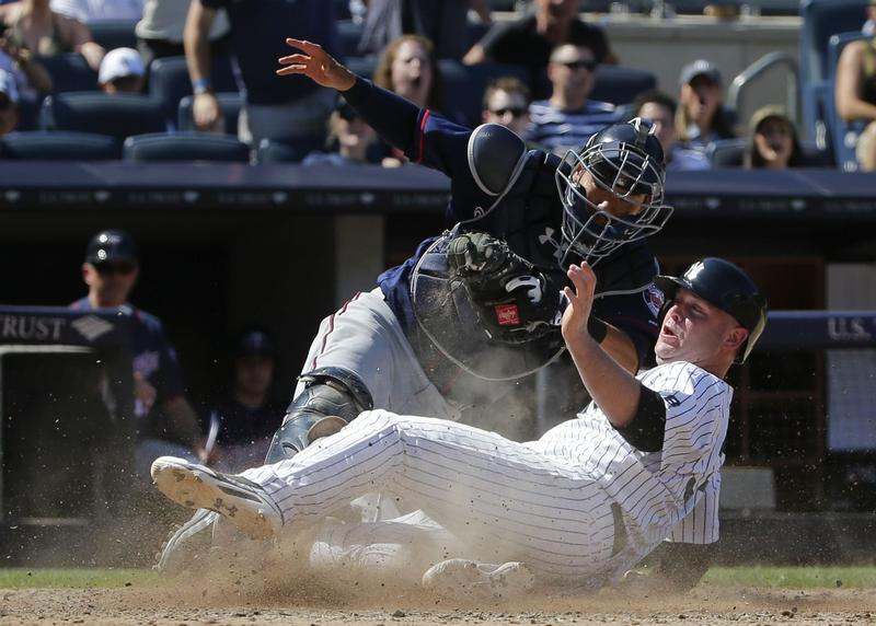 New York Yankees' Brian McCann, right, is tagged out at home plate by Minnesota Twins catcher Kurt Suzuki during the eighth inning of a baseball game Saturday, June 25, 2016, in New York. The Yankees won 2-1.
