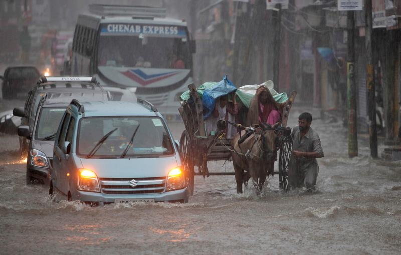An Indian man pushes a horse cart carrying passengers in the rain in Jammu, India, Wednesday, July 27, 2016. Monsoon season in India begins in June and ends in October.