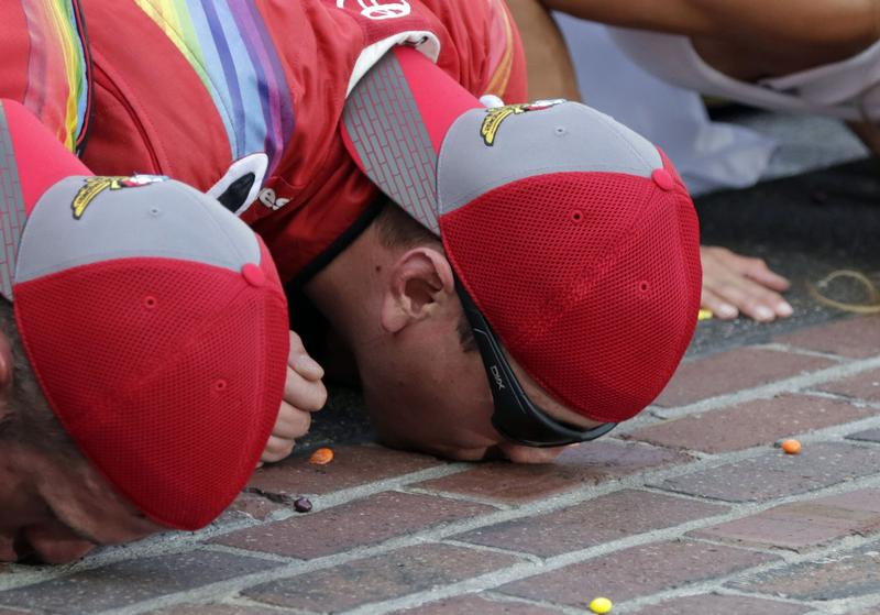 Kyle Busch, right, kisses the yard of brick at the start\finish line after winning the Brickyard 400 NASCAR auto race at Indianapolis Motor Speedway in Indianapolis, Sunday, July 24, 2016.