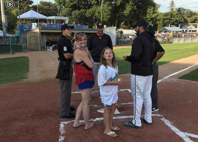 Mia joins Honkers field manager Trevor Hairgrove during the pre-game meeting with the umpires for Saturday's game versus Mankato