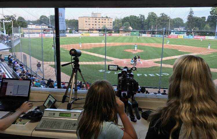 Mia helps operate a camera during Honkers' game from the Mayo Field press box on Saturday