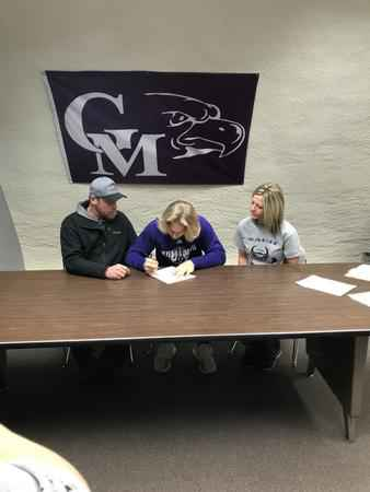 Grand Meadow football player Zach Myhre (center) signs with Winona State University on Wednesday morning